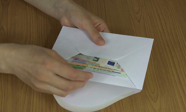 Θρίλερ: Άγνωστος πετά φακέλους γεμάτους χαρτονομίσματα κάτω από πόρτες σπιτιών